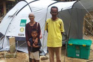 Mustafa musste sein Zuhause wegen eines starken Monsuns in Malaysia verlassen. Seine Familie steht vor einem ShelterBox Zelt, das sie im Zuge der Katastrophenhilfe erhalten haben.