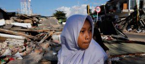 Menschen laufen in der Nähe der Ruine eines Geschäfts nachdem Erdbeben die Insel Lombok erschüttert haben.