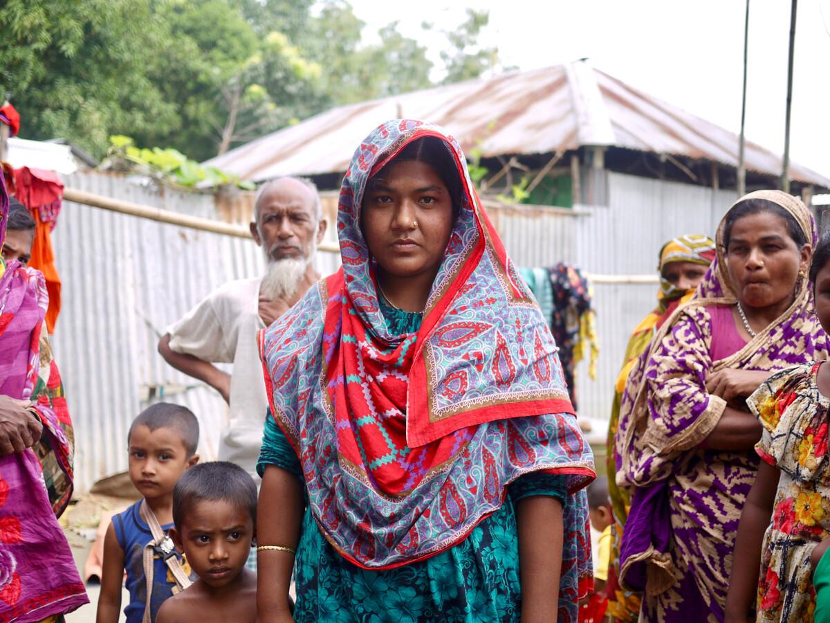 Eine Frau, umringt von anderen Frauen und Kindern, in farbenfroher Kleidung. Bild zeigt die Bewohner eines Dorfes in Bangladesch im Jahr 2017 nach einer Überschwemmung