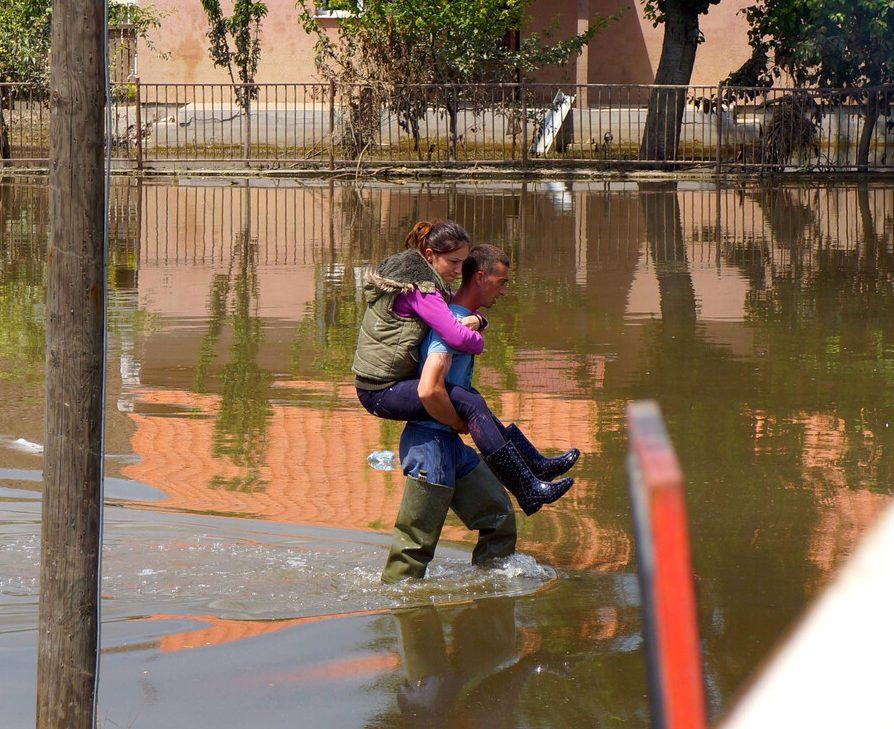 Ein Mann trägt eine Frau durch die Wasserfluten nach den Überschwemmungen in Serbien, 2014.