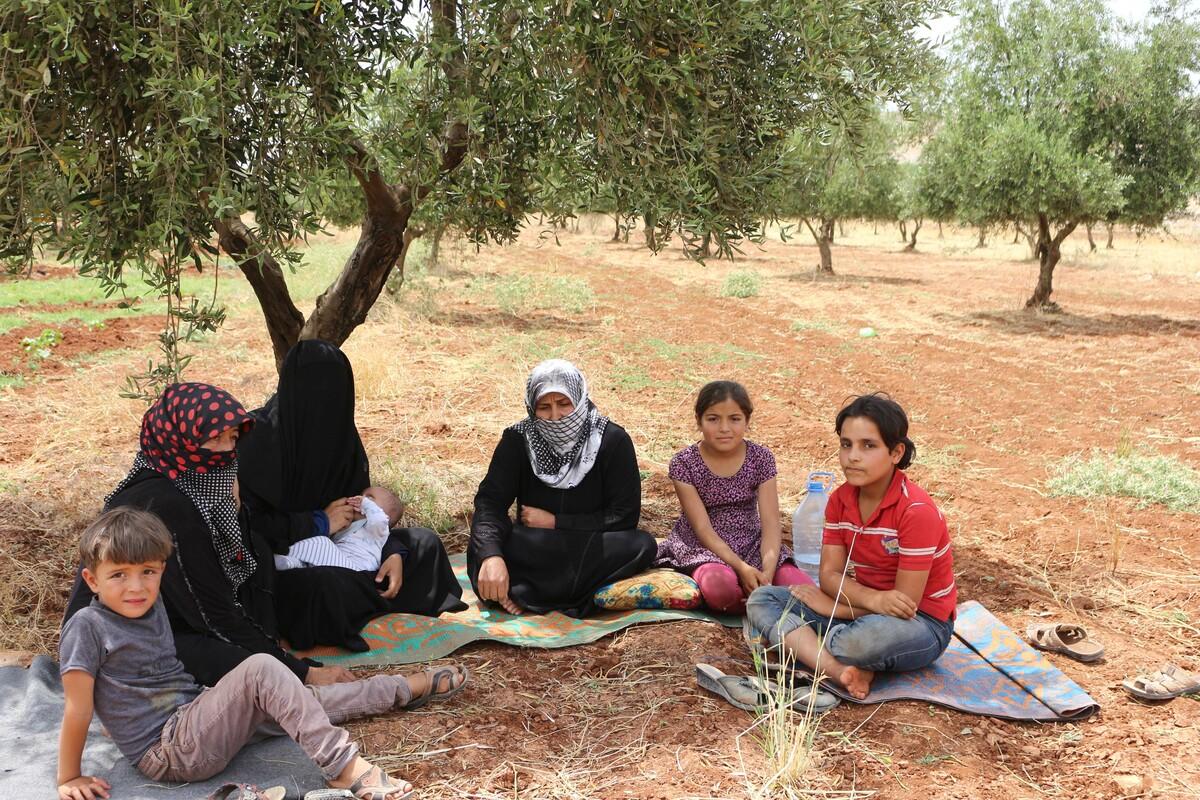 Familie in Syrien unter einem Baum sitzend