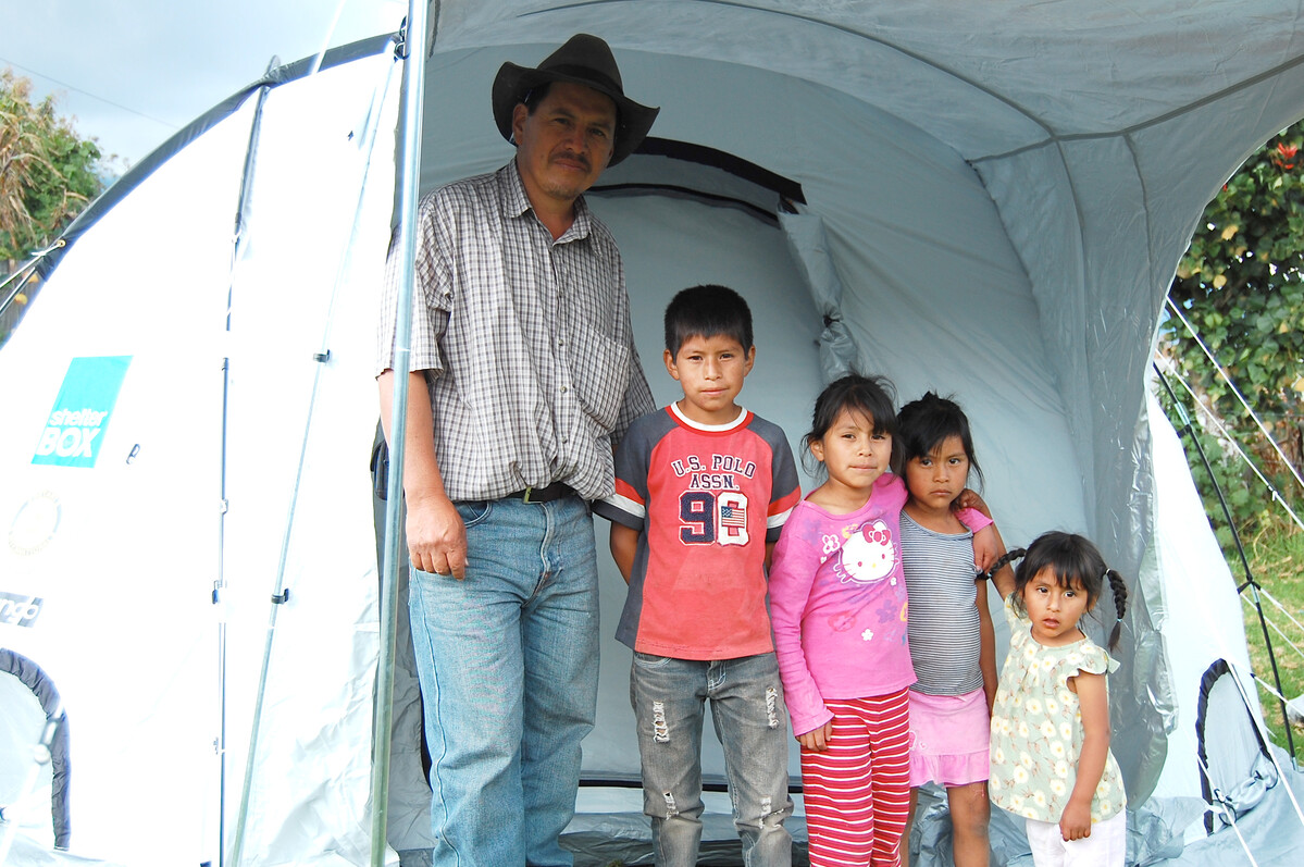 Ein Mann mit seinen Kindern vor einem ShelterBox Zelt nach dem Vulkanausbruch in Guatemala