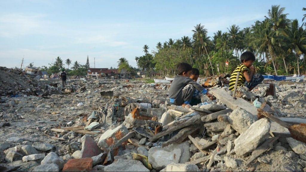 Kinder, die in Häuserruinen spielen, welche durch ein Erdbeben und einen Tsunami in Indonesien entstanden sind