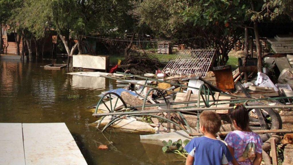 Kinder sitzen vor den Trümmern einer Überschwemmung
