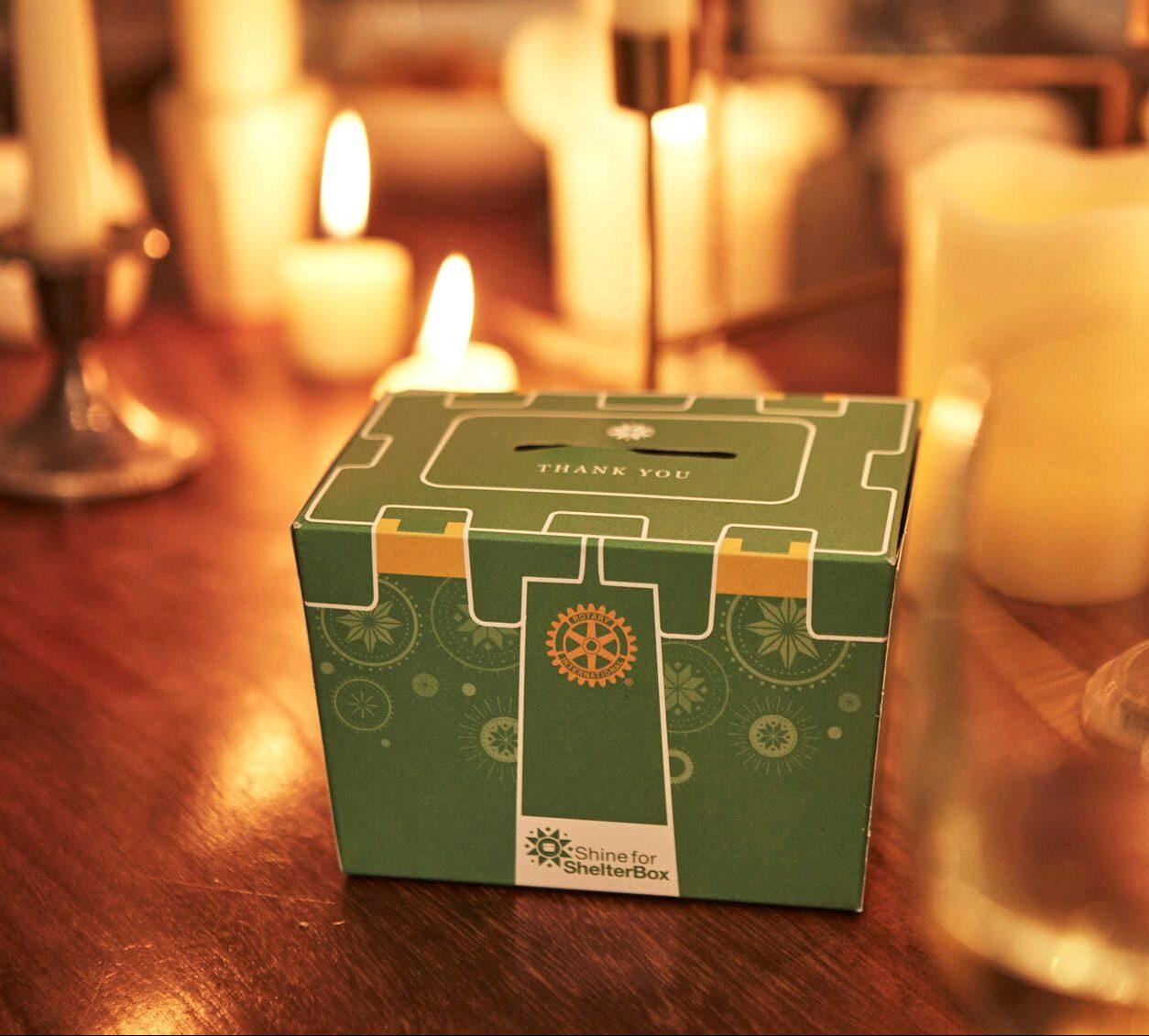 Eine Shine-For-ShelterBox Spendenkiste im Kerzenlicht