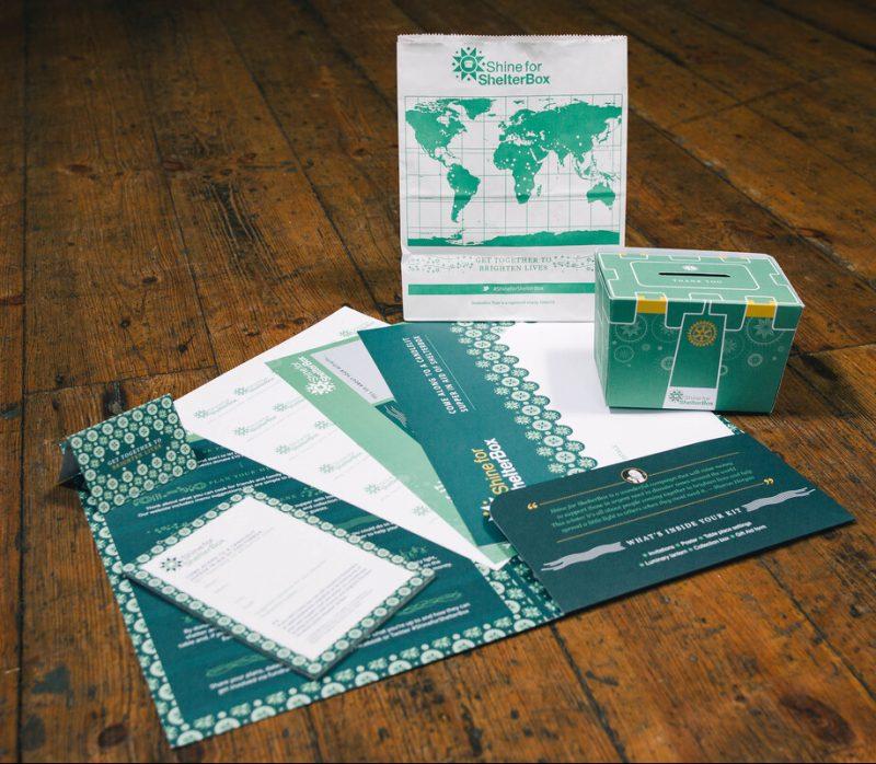 Shine-For-ShelterBox Spendenaktionspaket mit Spendenbox, Platzkarten und Geschichten von Betroffenen