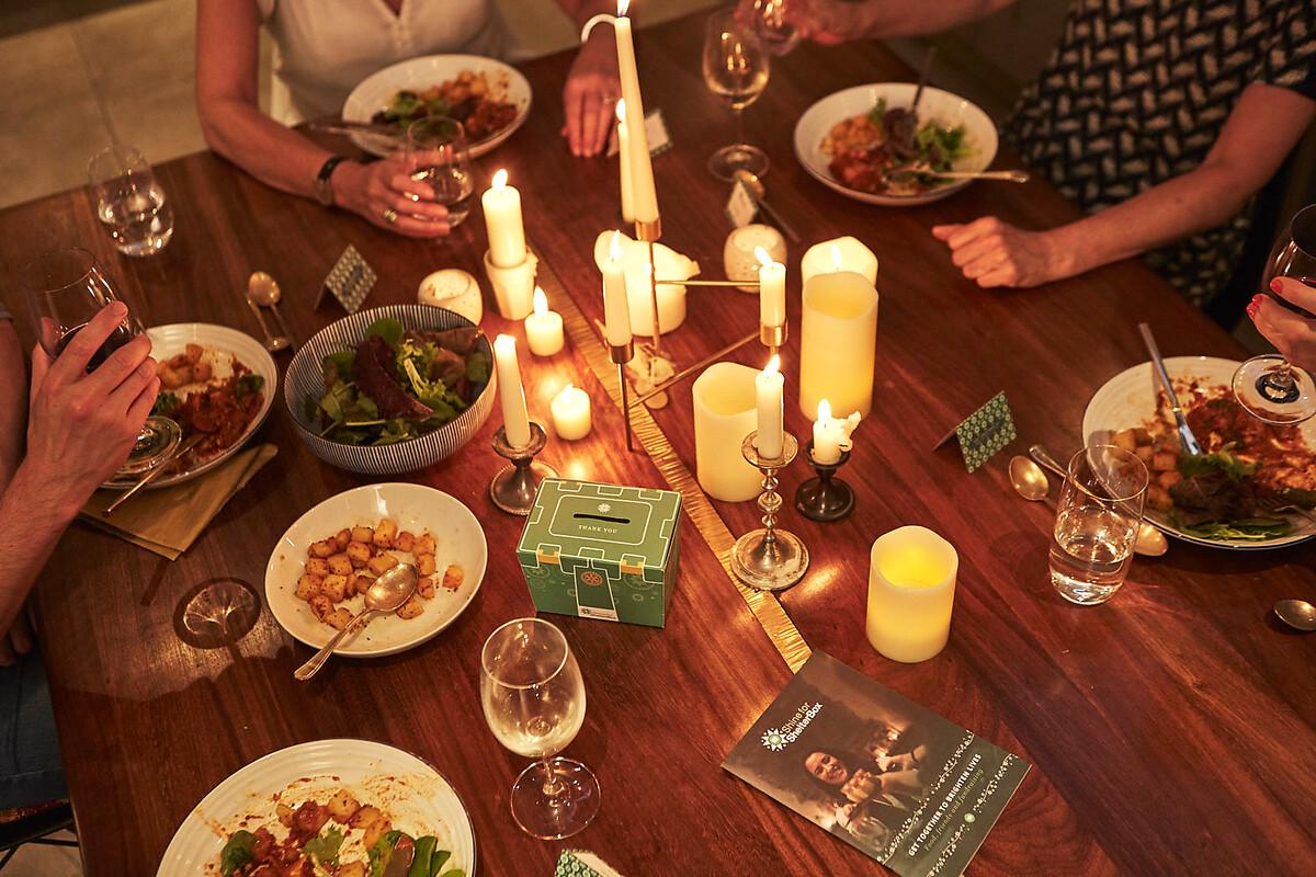 Menschen sitzen um einen Esstisch mit Kerzen
