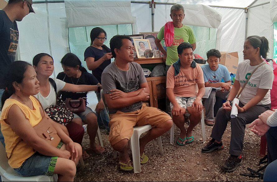 Menschen versammeln sich in einem Zelt in den Philippinen, um den Einsatz nach drei Erdbeben zu besprechen.