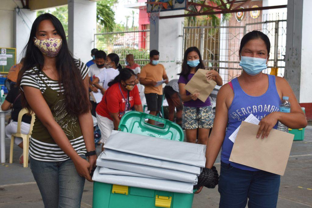 Familie trägt shelterbox auf den Philippinen