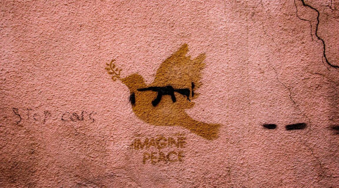 Street Art mit Friedenstaube und Maschinengewehr, Symbole für Krieg und Frieden