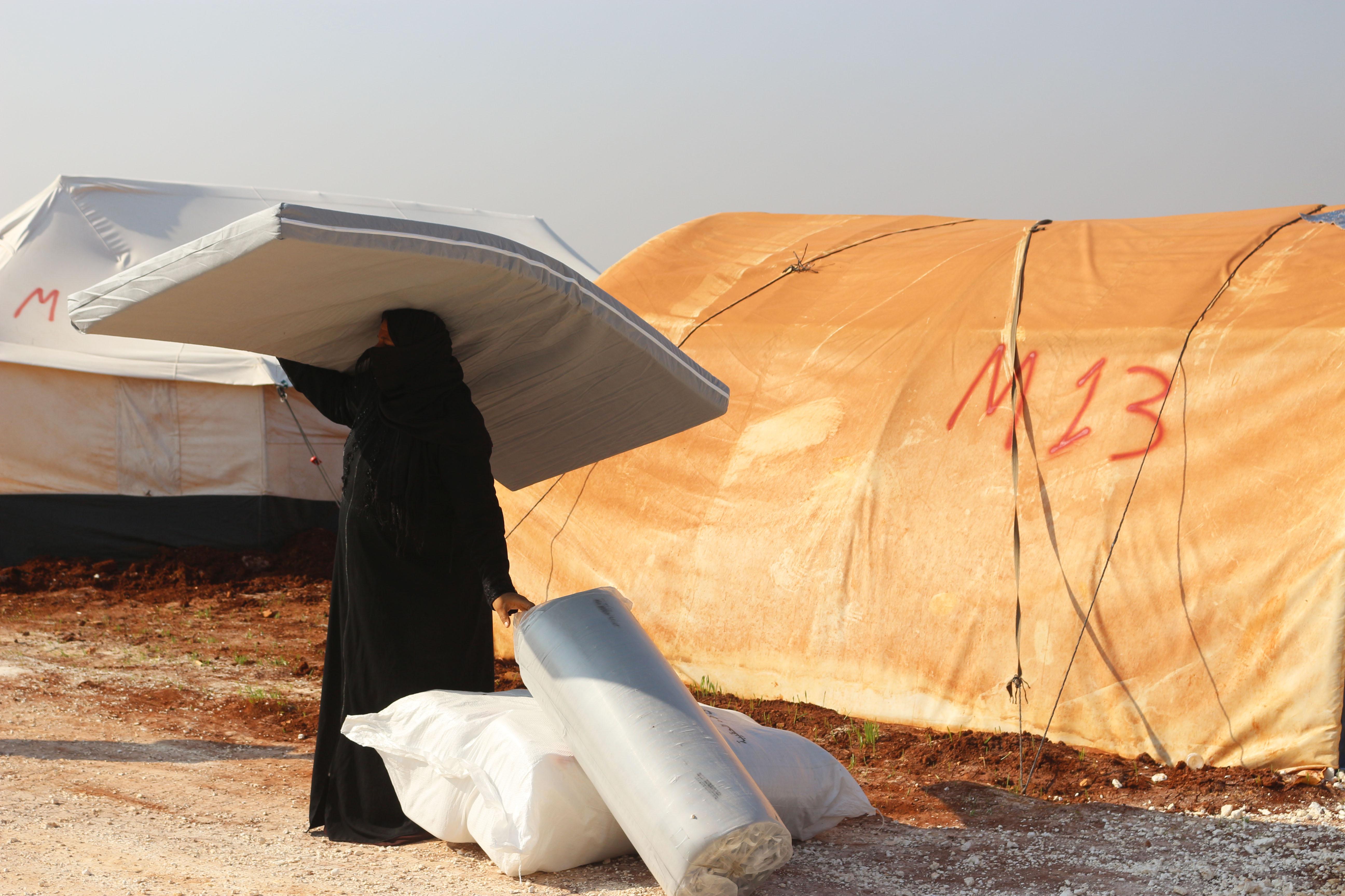 Binnenvertriebene: Eine Vertriebene Frau im Norden Syriens erhält Hilfsgüter von ShelterBox