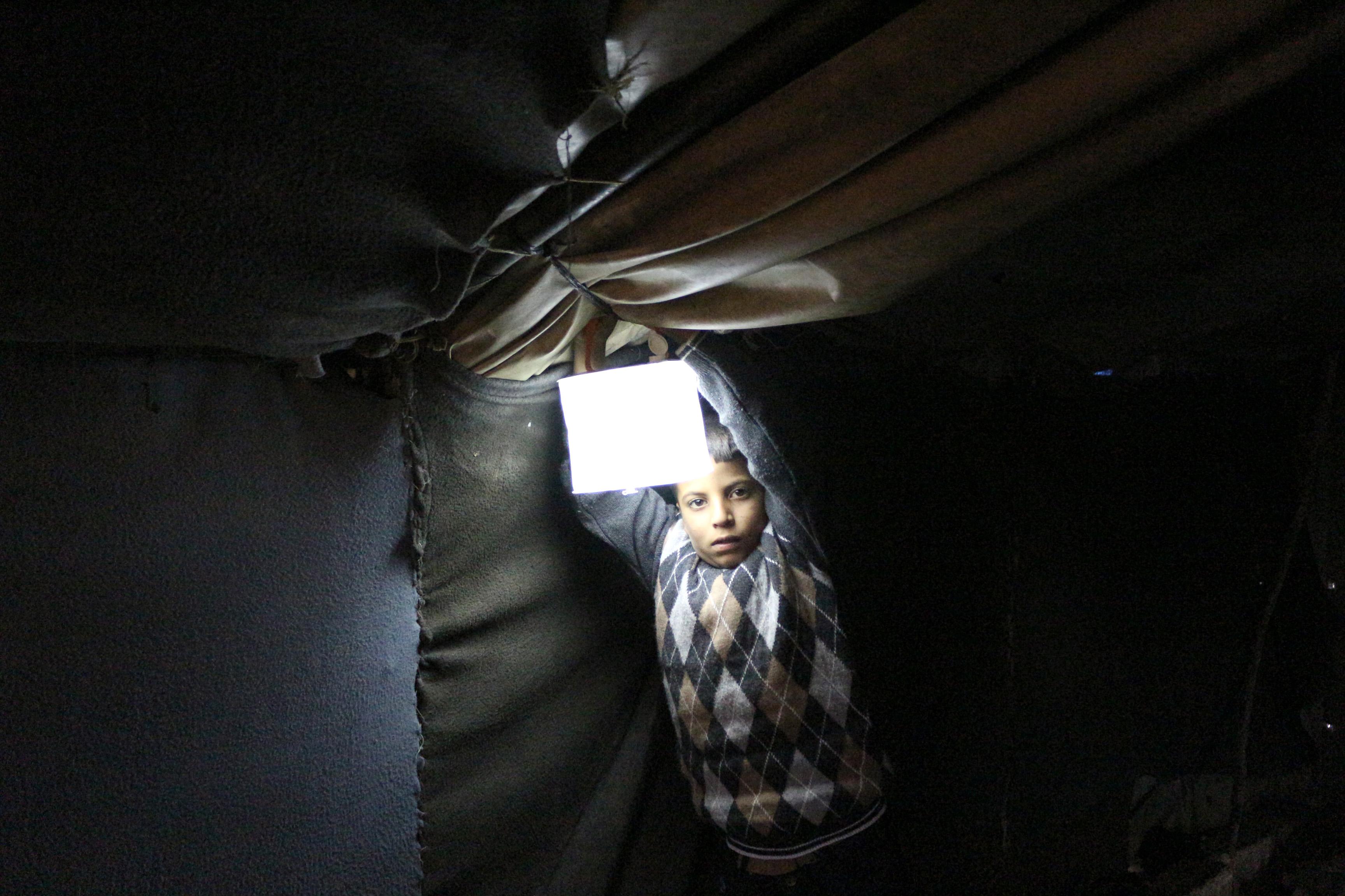 Binnenvertriebne: Ein Kind in Syrien mit einer Solarlampe von ShelterBox